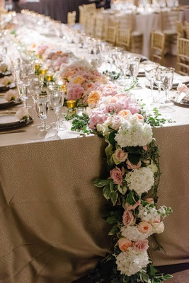 a cascading floral table runner featuring foliages and white pink and orange flowers