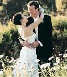 Bride and groom hug in white daisy field