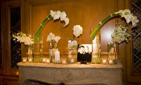 White flowers and candles on top of mantle