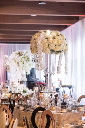 wedding reception centerpiece tall flower arrangement crystal vase orchid ivory hydrangea flowers
