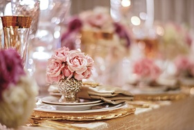 Pink roses in silver and gold vase on top of tablescape