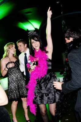 Wedding guests dancing in feather boas and hats