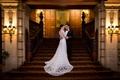 bride in lace v neck carolina herrera, groom in ralph lauren, hug on staircase