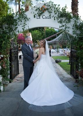 Bride in Oscar de la Renta a line wedding dress holding father of bride's hand before walking down