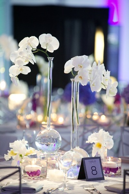 Long-neck vase with orchids at round reception table