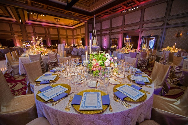 Ballroom wedding with gold charger plate blue napkin low centerpiece chair covers
