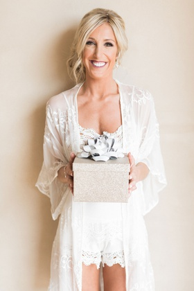 bride in getting ready robe holding gift box with big ribbon low bun white romper and robe