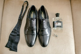 Groom's black dress shoes, bow tie, Creed cologne, silver cuff links