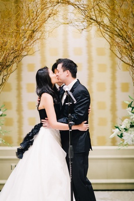 Bride in a strapless Vera Wang gown with a black bodice and white skirt kisses groom in black tuxedo