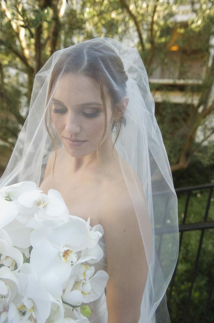 Bride in a veil holds white orchid bouquet