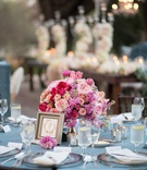 wedding reception table with dusty blue linens and small floral arrangement in shades of pink