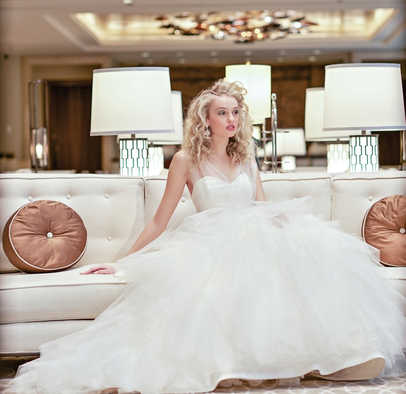 Bride in Alvina Valenta wedding dress on white couch
