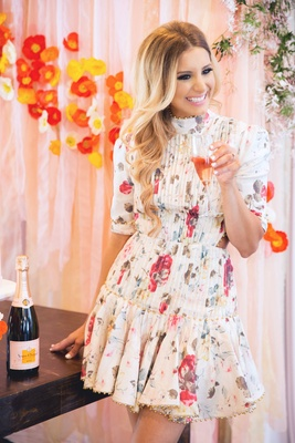 Bride in short flower print high neck cute dress holding champagne flute filled with rose poppies