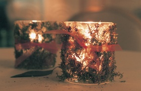 glass votive candleholders decorated with moss and orange ribbon