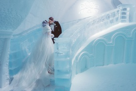 bride in sparkle wedding dress and cape with fur headpiece kiss groom ice staircase quebec city