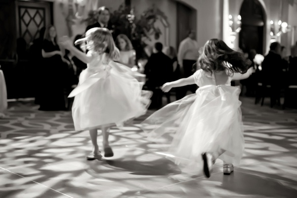 black and white photo of flower girls dancing at a reception