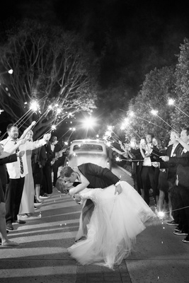 Black and white photo of bride being dipped by groom during firework sparkler exit getaway car