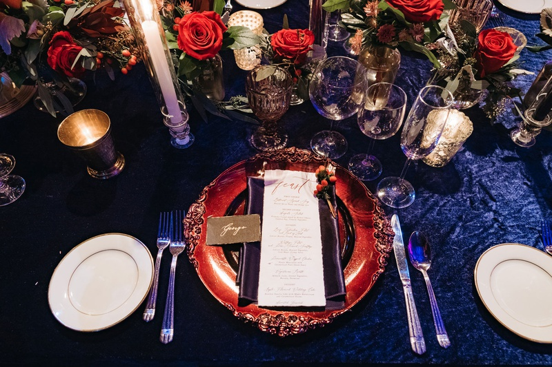 winter wedding tablescape decorations blue linens with scarlet rose flower arrangement centerpieces