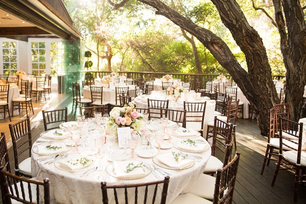 wedding reception outdoor tables light color palette low centerpieces roses wood chairs greenery