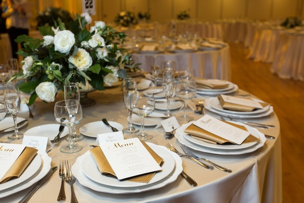 wedding reception, low centerpiece with greenery and white flowers, champagne linens, gold napkins,