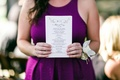 Guest holds white wedding ceremony program with banner monogram and pink hummingbirds