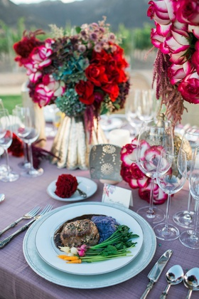 pink table linens gold vases red rose and purple floral arrangements gourmet food steak vineyard