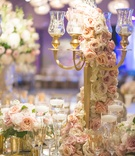 Wedding reception table with gold candelabra, light orange, purple, pink roses, white hydrangeas