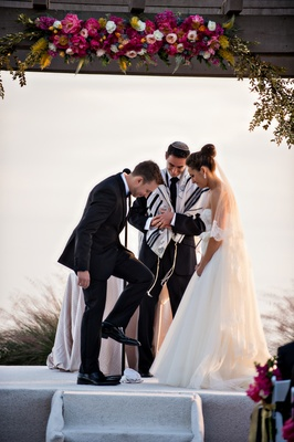 Groom steps on glass during outdoor oceanfront Jewish wedding
