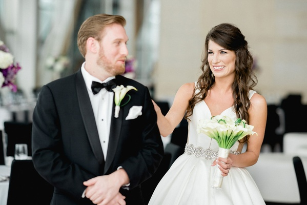 Bride walking up to groom and tapping him on shoulder during first look in reception space
