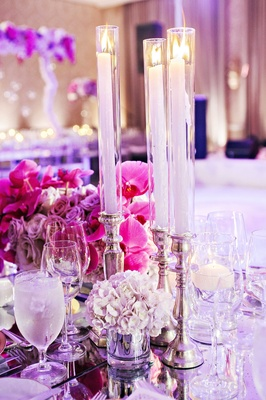 Hydrangea, orchid, rose purple low centerpieces with taper candles on top of silver candlesticks