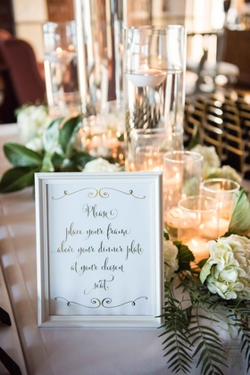 sign with instructions for getting escort cards, photobooth frames for favors
