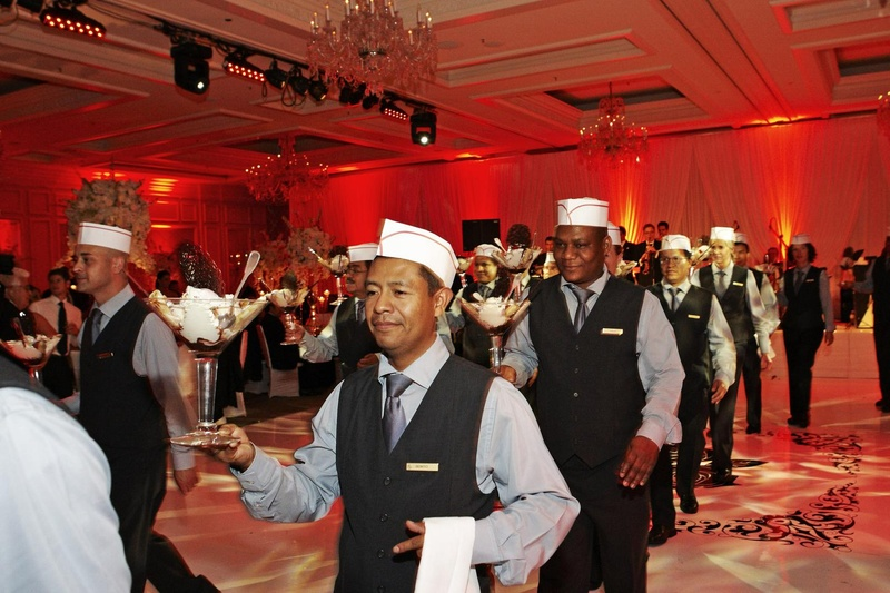 Waiters in paper hats delivering martini glass desserts