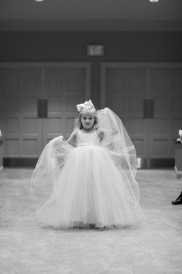 Black and white photo of a flower girl in a dress with straps and a tulle skirt.