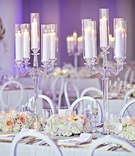 white candles in crystal candelabra, round back chairs, purple uplighting
