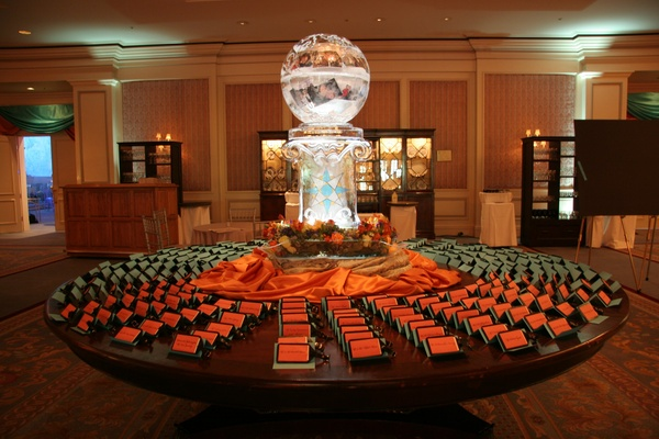 Wedding reception place card table with globe ice sculpture and orange and teal place cards