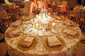 Round reception table with leaf linen and gold charger plates