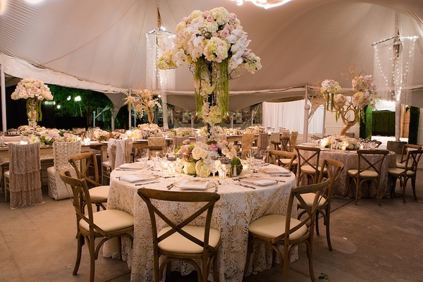 White lace tablecloth with rustic chairs and tall centerpieces