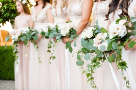 Bridesmaids in ivory and blush dresses with pretty garden flowers ivy and jasmine greenery neutral