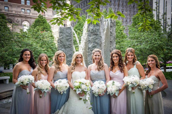 Bride in a strapless lace Isabelle Armstrong dress with bridesmaids in pastel Amsale and Jim Hjelm