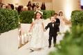 Wedding ceremony flower girl in vintage inspired dress ring bearer in tuxedo holding hands greenery
