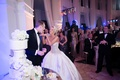 Bride in a strapless Ines Di Santo wedding dress with beaded bodice gives cake to groom in black tux