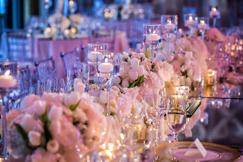 Wedding reception table with violet lighting, mirror top, white tulip, white pink rose, candles
