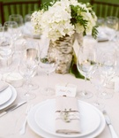 Outdoor wedding reception centerpiece with white hydrangeas and greenery