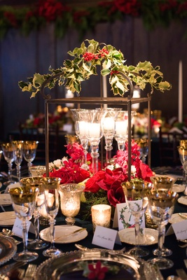 Candles in crystal candleholders with holly, greenery, and red flowers