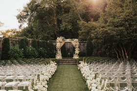 wedding ceremony on grass lawn seattle ghost clear chairs white flowers chuppah drapes neutral decor