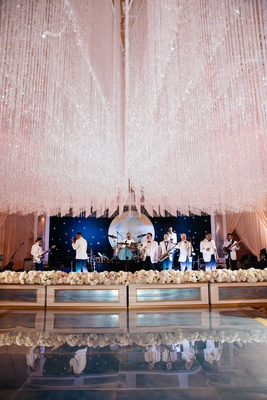 Wedding band in white tuxedo jackets performing under crystal ceiling treatment at ballroom wedding