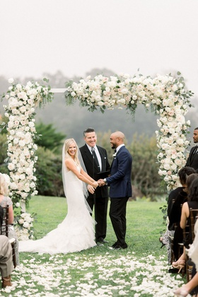 bride in mermaid wedding dress nfl player groom muted color flower arch grass lawn petals