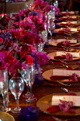 Long wedding reception table with purple flowers