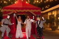 CJ Lana Perry and Miroslav Rusev Barnyashev at circus theme wedding running under red circus tent