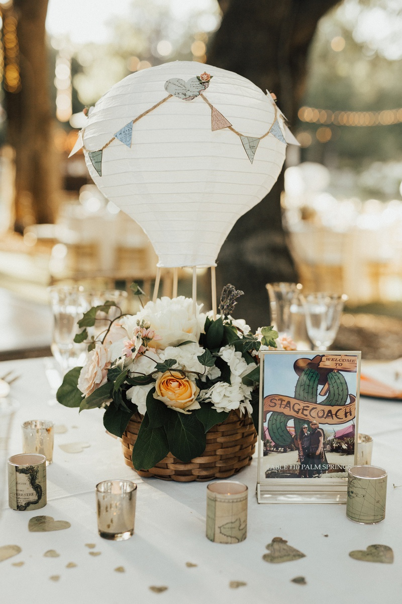 paper lantern hot air balloon wedding centerpiece surrounded by votive candles wrapped with maps